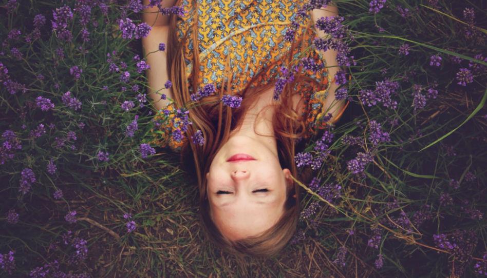 Hier ist eine junge Frau zu sehen, die auf einer Blumenwiese liegt.