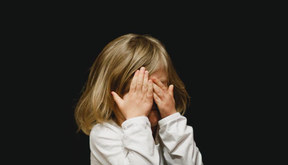 Auch Kinder haben Herausforderungen im Leben. Auf diesem Bild ist ein junges Mädchen zu sehen, das sich mit den Händen die Augen zuhält, als würde es ihre Tränen verstecken wollen.