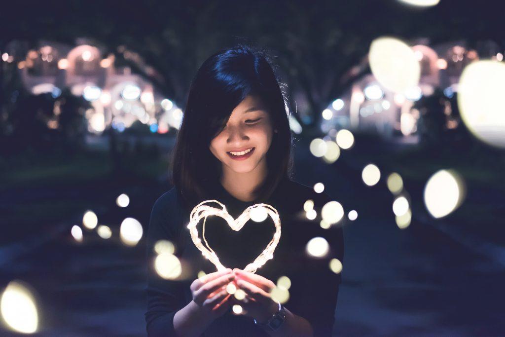 Auf diesem Bild ist eine junge Frau zu sehen, die ein leuchtendes Herz in der Hand hält, welches sie lächelnd anschaut.