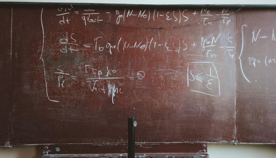 Zu sehen ist eine alte Tafel, auf der eine Gleichung zu lesen ist.
