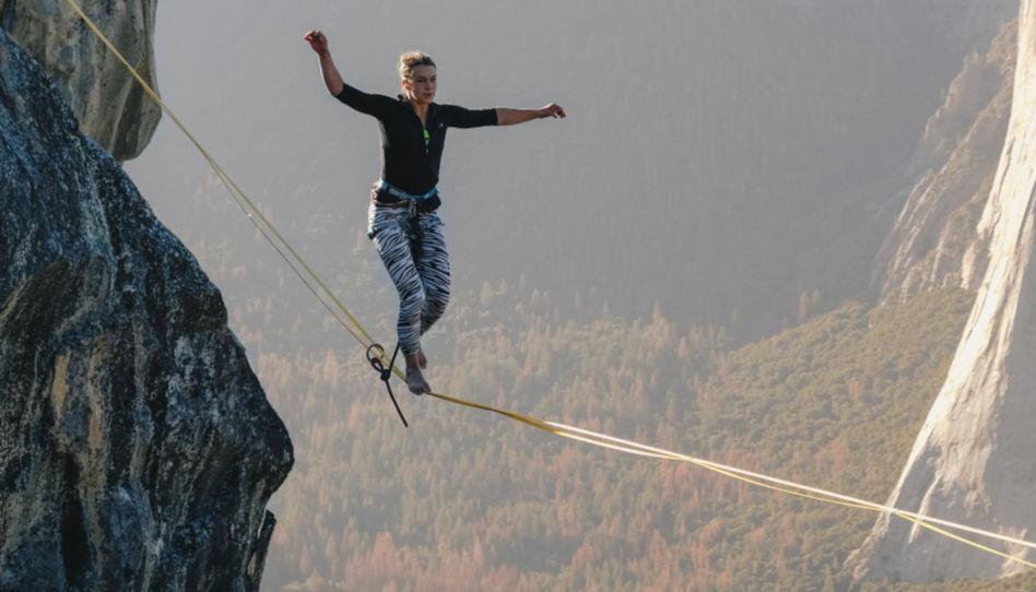 Hier ist eine junge Frau zu sehen, die in luftiger Höhe auf einem Seil balanciert.