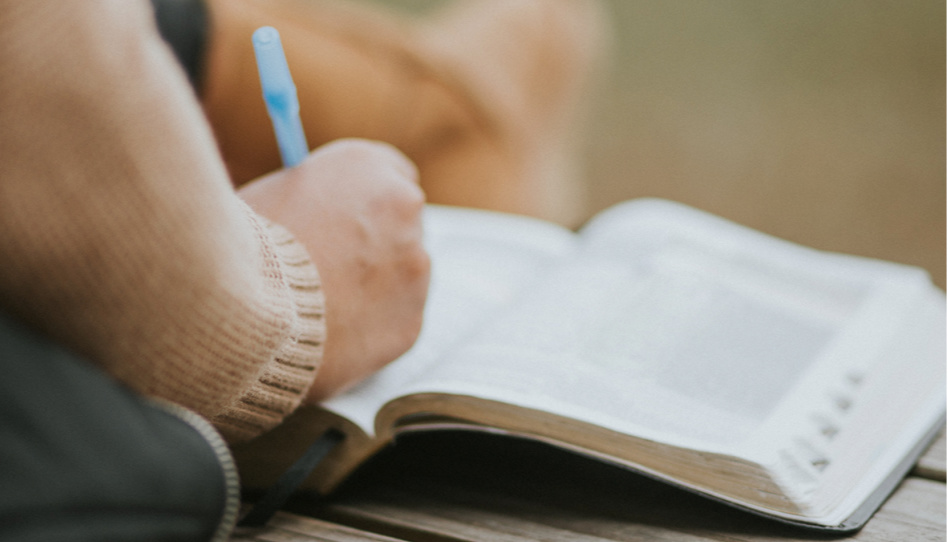 Man sieht die Hand einer Person, die mit einem Stift etwas in eine Bibel schreibt.