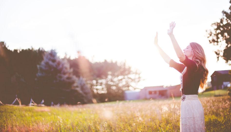 Eine junge Frau steht mit geschlossenen Augen auf einer Wiese, und hebt beide Hände in die Luft, als wolle sie sich bei ihrem himmlischen Vater bedanken.