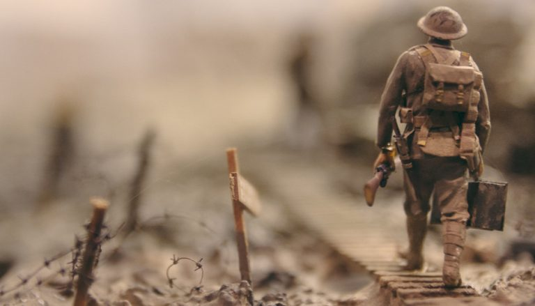 Hier ist ein Soldat mit einem Gewehr in der Hand zu sehen (von hinten). In einer Zeit der vielen Unruhen, Anschläge und Katastrophen fällt es vielen Menschen schwer, Optimismus zu haben.