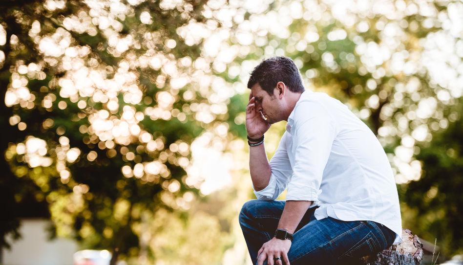Hier sitzt ein Mann auf einem Baumstumpf, die rechte Hand vor das Gesicht gehalten. Es sieht aus als würde er trauern.