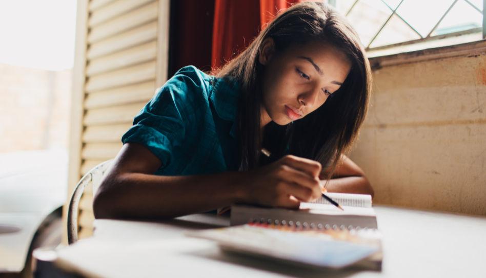 Eine junge Frau studiert in den heiligen Schriften. Sie markiert oder schreibt etwas.