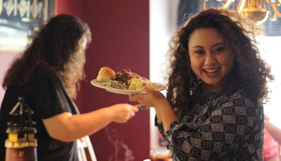Zu sehen sind zwei Frauen. Eine von ihnen hält strahlend ihren mit Essen gefüllten Teller in den Händen.