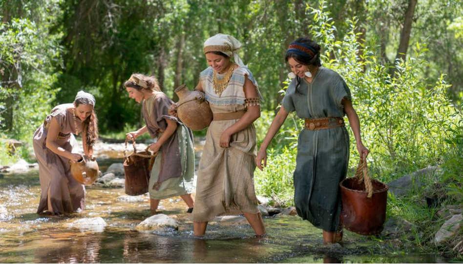 Zu sehen sind 4 Frauen, die an einer Quelle Wasser schöpfen. Es handelt sich um eine Szene in den neuen Buch-Mormon-Videos.