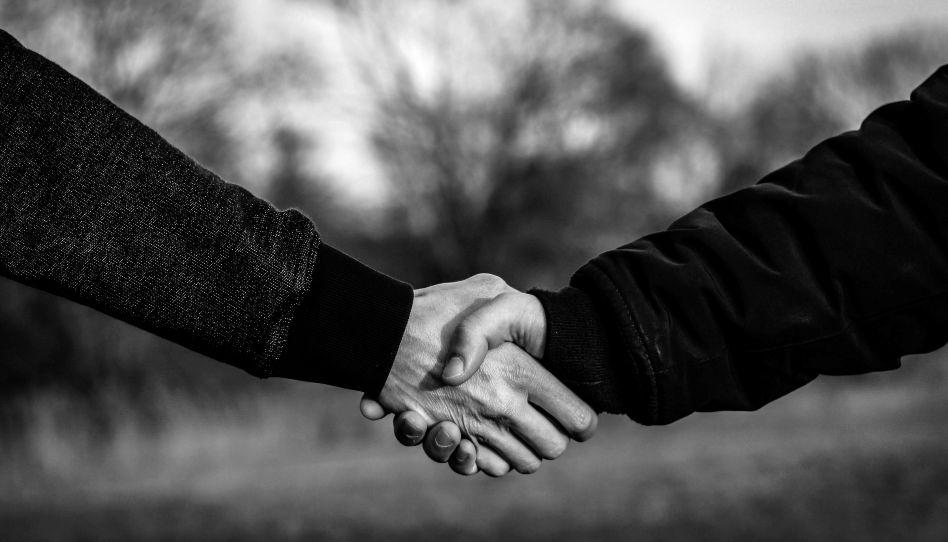 Zu sehen ist ein Handschlag. - Die Wahrheit zur Aussage: Zu vergeben bedeutet, deinen Feind zu lieben.