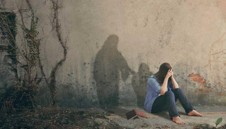 Zu sehen ist eine auf dem Boden sitzende junge Frau, die ihr Gesicht hinter ihren Händen versteckt. Sie scheint traurig zu sein. An der Wand in ihrem Rücken sieht man links von ihrem Schatten einen weiteren Schatten, welcher ihr die Schulter tätschelt, Jesus Christus. In diesem Beitrag erfahren wir sehr private Einblicke von jungen Menschen, die uns zeigen können wie es ist, Jesus zu begegnen, wenn wir ihn am dringendsten brauchen.