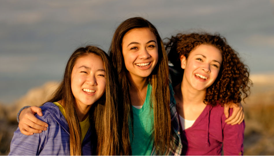 Zu sehen sind drei junge Frauen, die sich im Arm haben und in die Kamera strahlen.