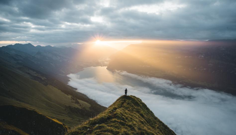 Zu sehen ist eine wunderschöne bergige Landschaft, unten Wolken, im Hintergrund scheint die Sonne hindurch. Im Vordergrund, aber immer noch ziemlich klein, ist eine Person auf einem Felsvorsprung zu sehen.