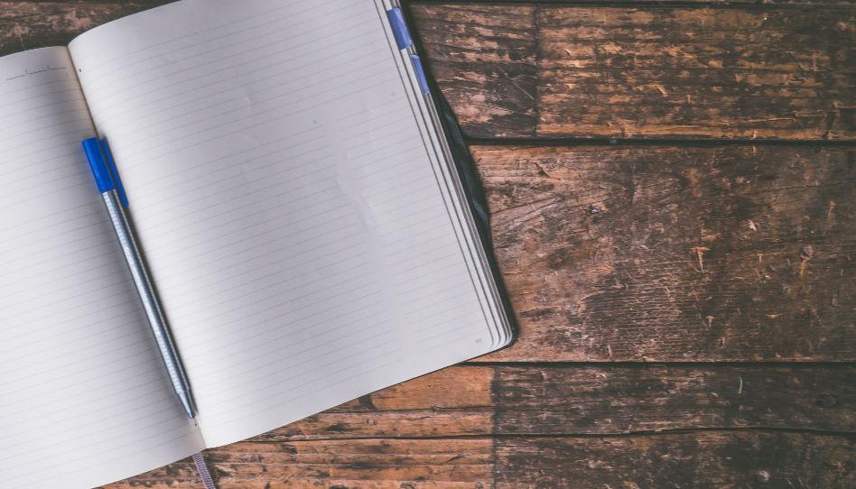 Zu sehen ist ein aufgeschlagenes, noch unbeschriebenes Notizbuch, auf welchem ein Stift liegt.
