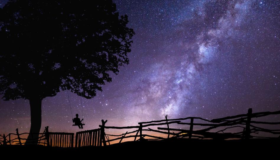 Zu sehen ist die Aufnahme eines wunderschönen Sternenhimmels. Im Vordergrund sieht man jemanden schaukeln.