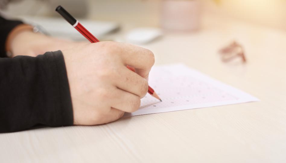 Zu sehen ist eine Hand, die einen Bleistift in der Hand hält. Es scheint, als würde ein Test geschrieben. - Die Wahrheit über die Aussage: Gott gab mir diese Prüfung, damit ich etwas lerne.
