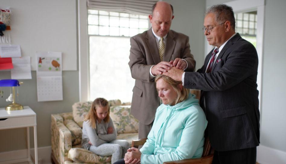Eine Frau sitzt mit geschlossenen Augen auf einem Stuhl, ihre Tochter im Hintergrund auf einer Couch. Zwei Priestertumsträger haben der Frau die Hände auf den Kopf gelegt, um ihr einen Segen zu geben.