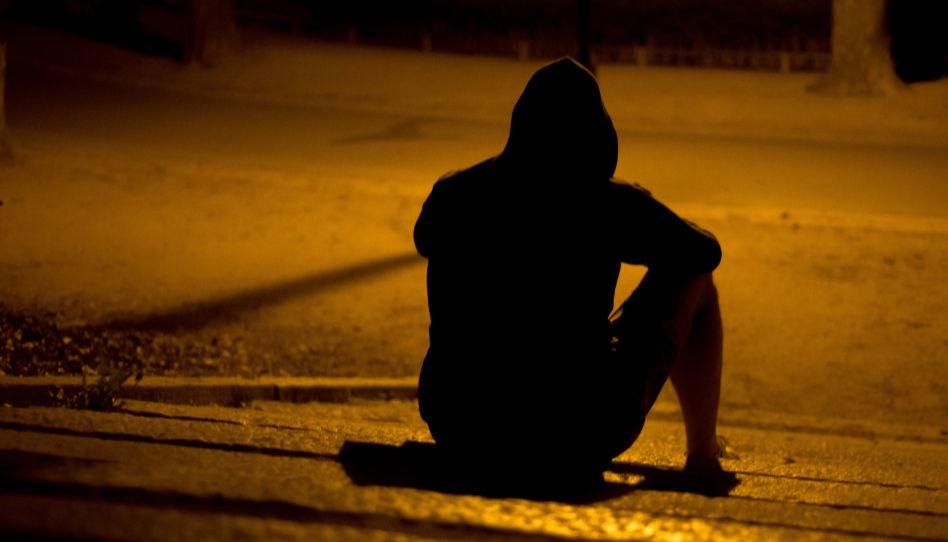 Zu sehen ist die Silhouette eines sitzenden Mannes von hinten im Dunkeln.