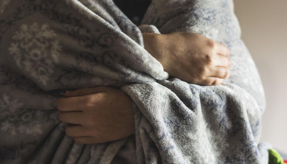 Ein Körper ist in eine Decke eingehüllt und zwei Hände halten die Decke.