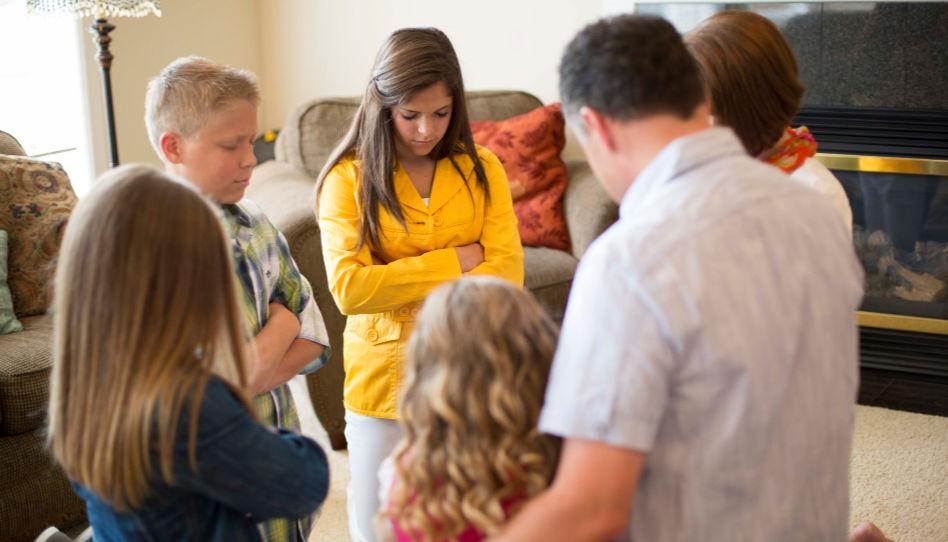 Zu sehen ist eine Familie beim Gebet.
