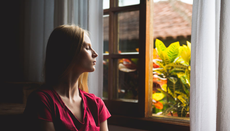 Zu sehen ist eine Frau die entspannt aus dem Fenster schaut.
