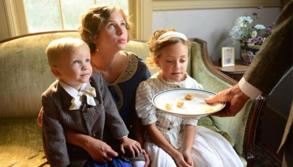 """Zu sehen ist die Schauspielerin Cassidy Hubert in ihrer Rolle als Rebecca Bean, mit """"ihren"""" zwei Kindern auf dem Schoß."""