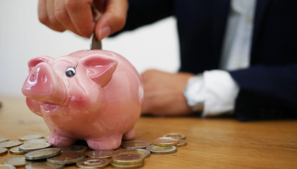 Zu sehen ist ein Sparschwein, in welches Geld geworfen wird.