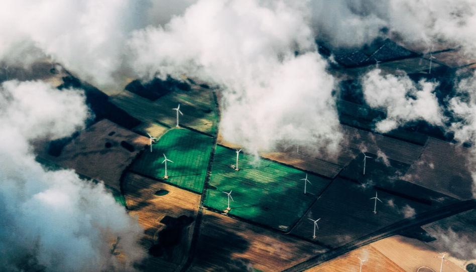 Durch ein paar Wolken hindurch, schaut man aus der Vogelperspektive auf Felder, die mit Windrädern bestückt wurden. Diese stehen ja unter anderem symbolisch für den Umweltschutz.