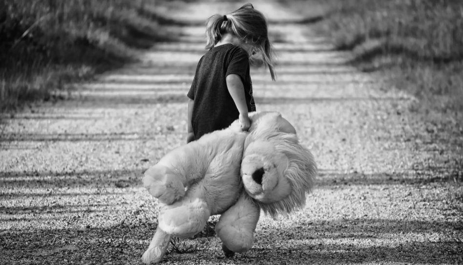 Zu sehen ist ein junges Mädchen, die ein riesiges Kuscheltier in der Hand hält und sich etwas wegdreht. Kinder haben auch einen emotionalen Hunger, der ebenso befriedigt werden muss, wie der nach Nahrung.