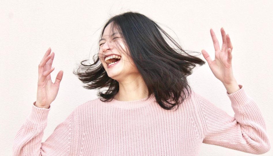 Zu sehen ist eine junge lachende Frau.