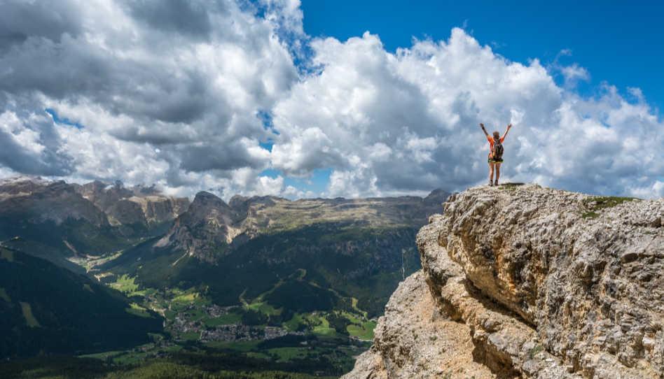 Zu sehen ist eine Frau, die einen Gipfel bestiegen hat, auf einem Felsen steht und sich mit erhobenen Armen freut.