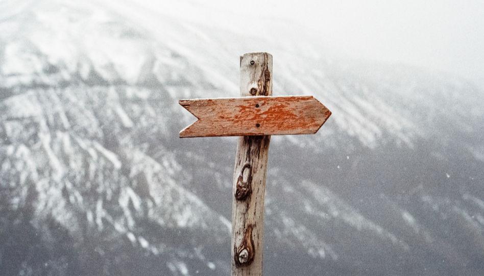 Zu sehen ist hier ein richtungsweisender Pfeil aus Holz, der in einen Stamm genagelt wurde. Das soll symbolisch für die Ordnung stehen, welche im Haus des Herrn herrscht.