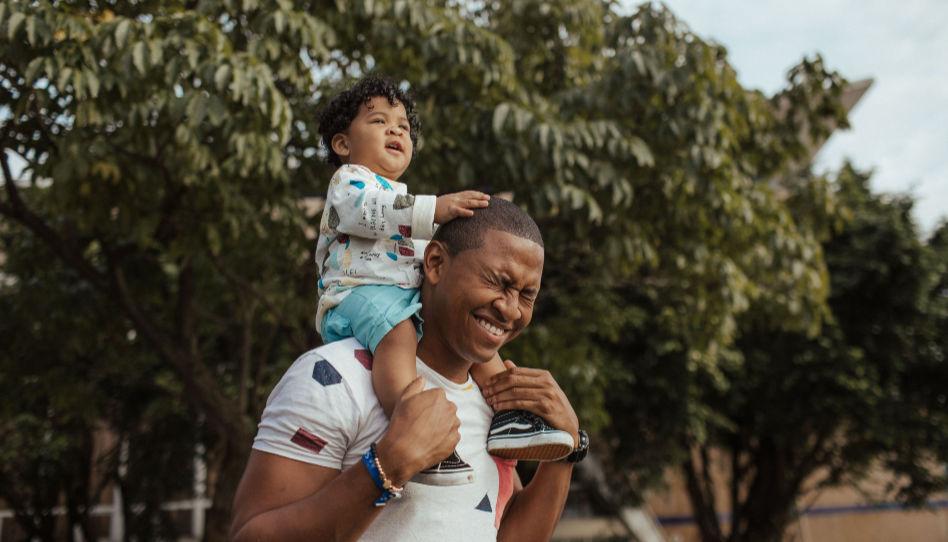 Zu sehen ist ein Vater, der seinen kleinen Sohn auf den Schultern trägt und dabei lacht.