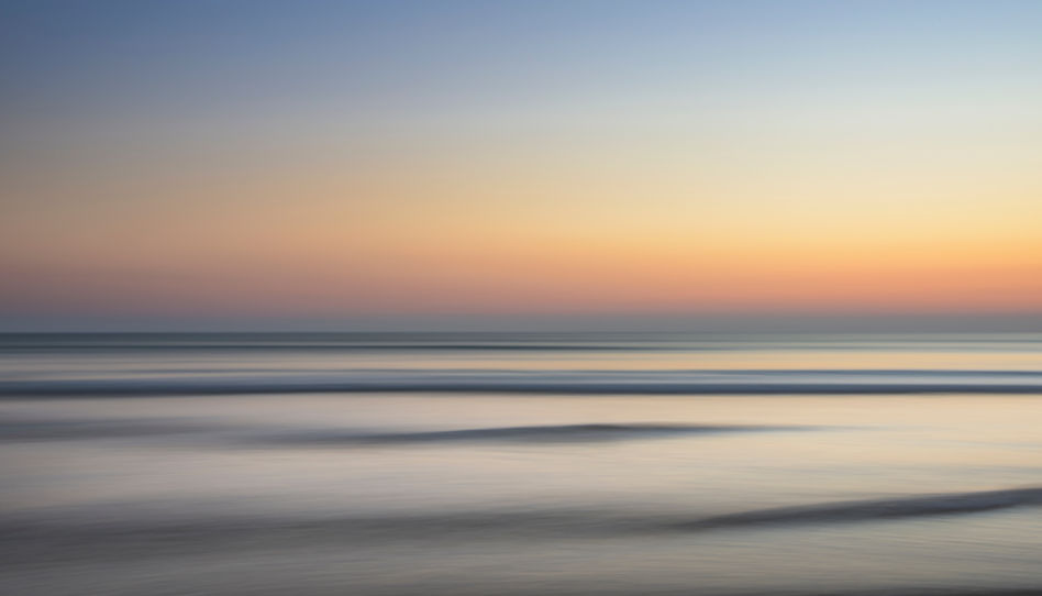 Zu sehen ist das Meer und im Hintergrund wunderschöne Farben im Himmel, durch einen Sonnenuntergang.