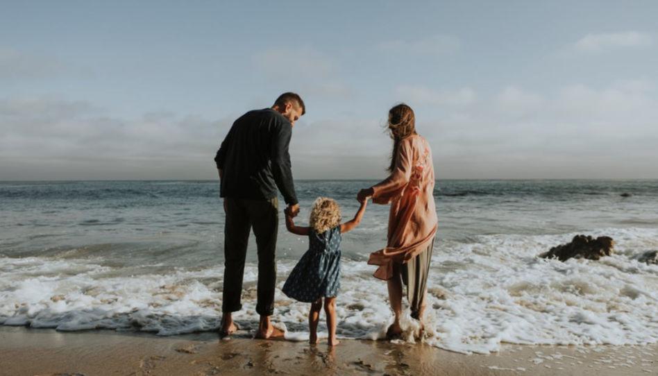 Zu sehen sind ein Vater und eine Mutter, die ihre Tochter in ihrer Mitte an der Hand halten, während sie am Strand stehen, das Meer vor ihnen.