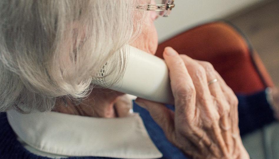 Zu sehen ist eine ältere Frau, die einen Telefonhörer in der Hand hält.