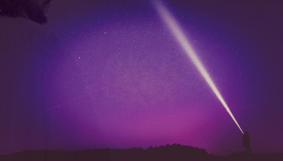 Eine Person leuchtet mit einer Taschenlampe in einen Sternenhimmel. Der Strahl lecuhtet sehr. Auf der linken Seite des Bildes sieht man ganz leicht einen Teil der Silhouette von Jesus Christus. Angst und Glaube werden oft mit Dunkelheit und Licht verglichen, daher dieses Bild.
