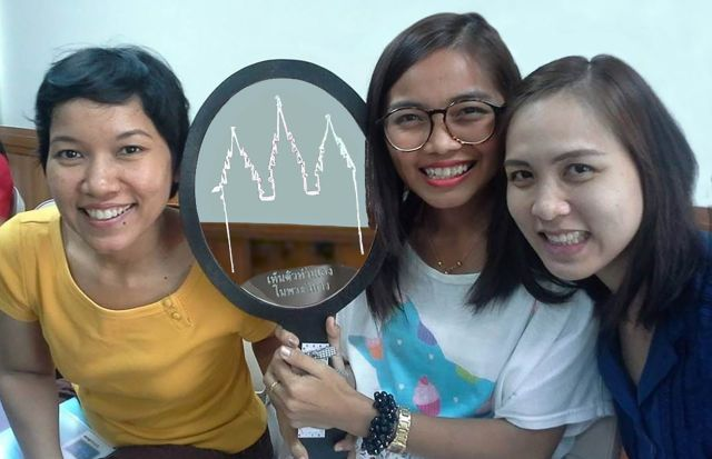 """Zu sehen sind drei junge Frauen aus Thailand, die einen Spiegel in der Hand halten. Auf dem Spiegel ist die Silhouette eines Tempels zu sehen und unten steht """"Sehen Sie sich selbst im Tempel"""" geschrieben."""