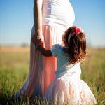 Zu sehen ist ein kleines Mädchen, das vor seiner schwangeren Mutter steht, zu dieser aufschaut und ihre Ahnd hält.