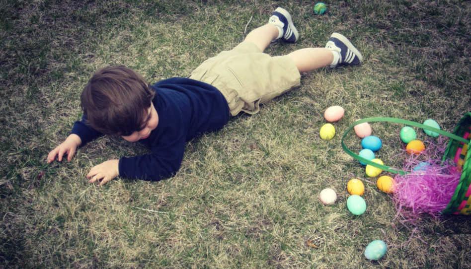 Zu sehen ist ein etwa dreijähriger Junge, der scheinbar mit seinem Korb voller Ostereier gestolpert ist.