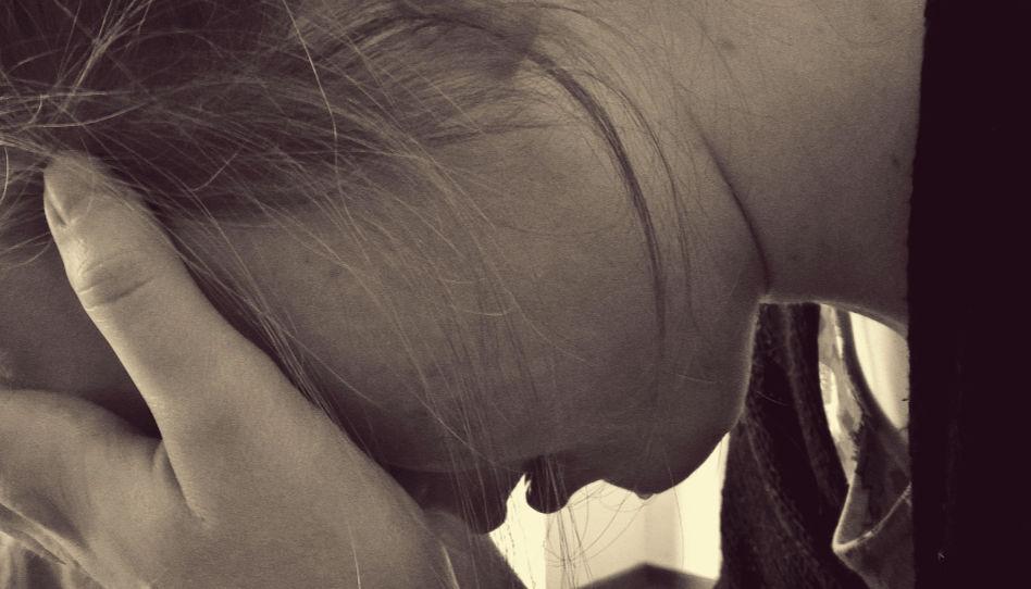 Zu sehen ist eine weinende Frau, die verzweifelt scheint. Stress ist einer der Hauptfaktoren für das Gefühl der Hilflosigkeit.
