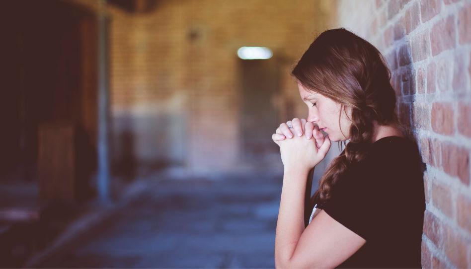 Auf diesem Bild ist eine Frau zu sehen, die mit dem Rücken an einer Hauswand lehnt und betet. Sie scheint verzweifelt zu sein.