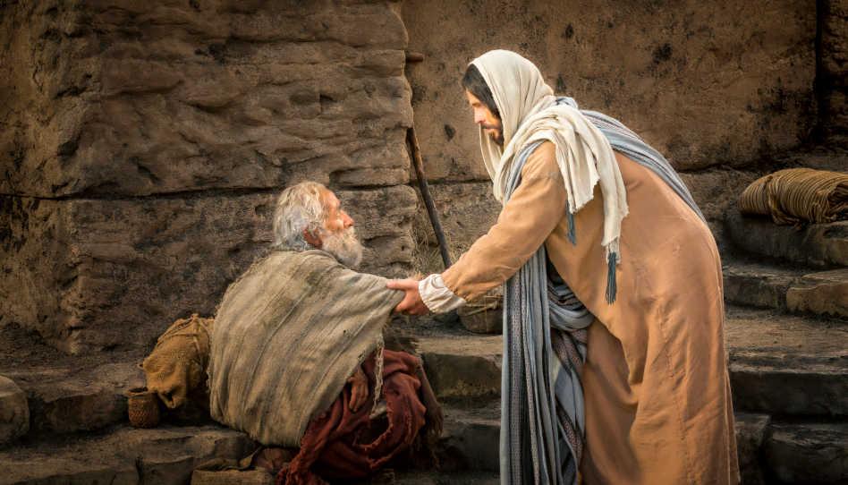 Jesus Christus hilft einem älteren Mann hoch, den er soeben geheilt hat.