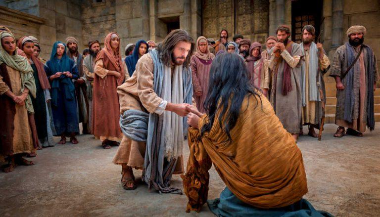 Jesus Christus beugt sich zu einer Frau runter und hält ihre Hand.