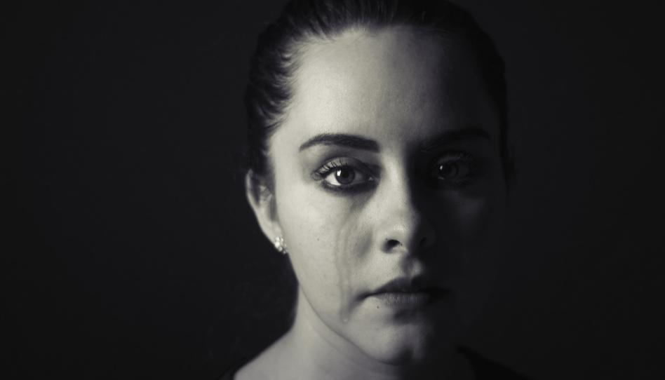 Zu sehen ist das Gesicht einer Frau, der eine Träne über die Wange läuft. Das Bild ist schwarz und weiß.