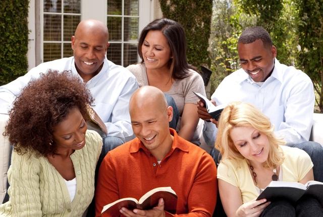 Eine Familie liest zusammen in den heiligen Schriften. Sie haben sichtlich Freude daran.