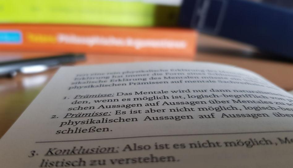 Zu sehen ist ein aufgeschlagenes Buch mit Fachliteratur. Im Hintergrund kann man weitere Bücher erahnen.