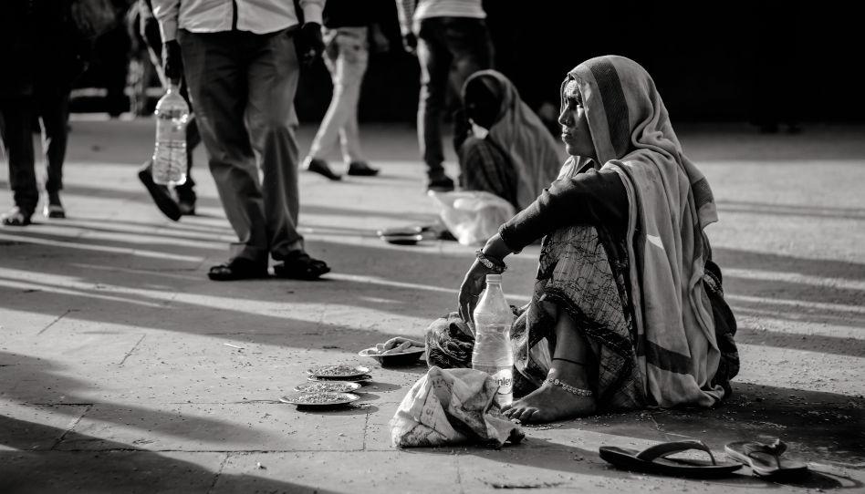Zu sehen ist eine Bettlerin, die auf der Straße sitzt.