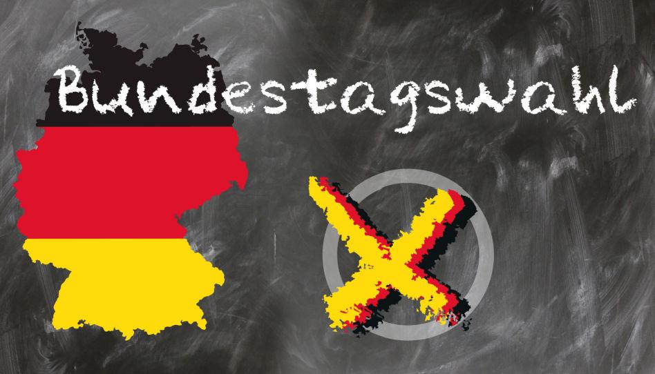 """Auf diesem Bild ist in weißen Lettern das Wort """"Bundestagswahl"""" zu lesen. Desweiteren sieht man die Karte Deutschlands in schwarz, rot und gold, sowie ein Kreuz auf einem Kreis."""