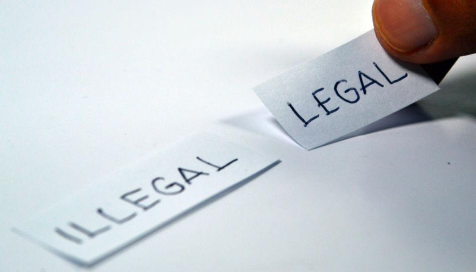 """Auf diesem Bild sind zwei Zettel zu sehen. Einer mit der Aufschrift """"illegal"""", der andere mit der Aufschrift """"legal""""."""