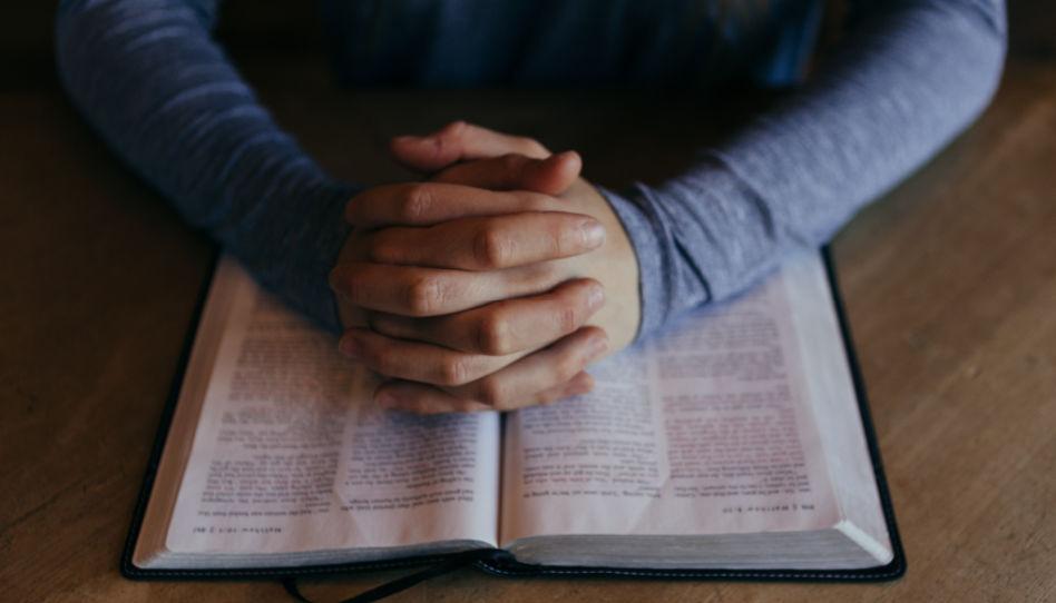 Zu sehen sind wie zum Gebet gefaltene Hände auf einer Bibel.